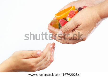 Hands of mother give colorful candies and sweets in hands child closeup - stock photo