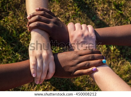 Hands of multiracial friends holding each other as team, cooperation concept - stock photo