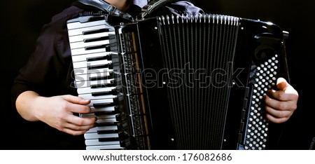 Hands of musician accordionist  and  frayed keys of  accordion - stock photo