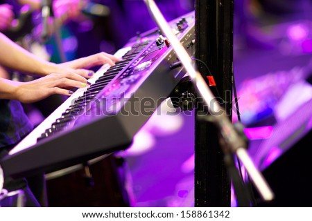 hands of musician playing keyboard in concert with shallow depth of field, focus on right hand - stock photo