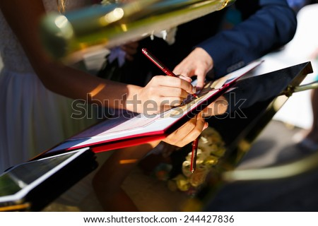 Hands of newlyweds of registration form on the wedding ceremony - stock photo