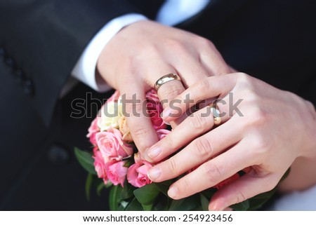 Hands of newlyweds with rings of white gold. Wedding rings. Bride and groom at the wedding. Hands of the bride and groom at a wedding bouquet. Bouquet of roses and hands with rings.  - stock photo