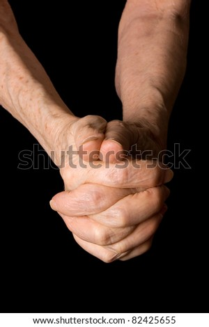 Hands of old woman on black background