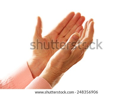 Hands of old woman on light background