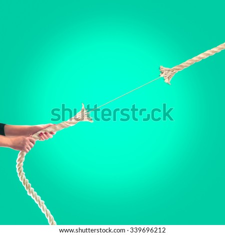 Hands of people pulling the rope on a green background.    - stock photo