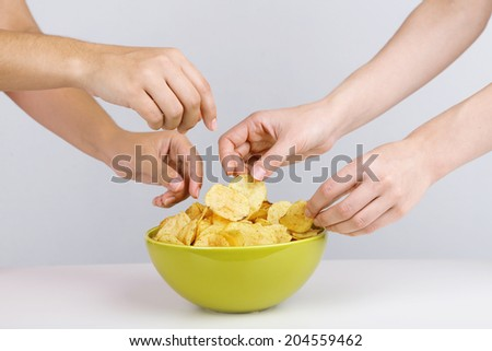 Hands of people take chips from bowl - stock photo