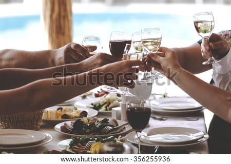 Hands of people with glasses of champagne or wine, celebrating and toasting in honor of the wedding or other celebration. - stock photo