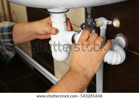 Hands of plumber assembling sink pipes, close up view