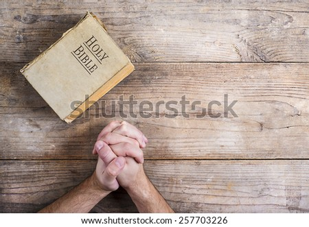 Hands of praying young man and Bible on a wooden desk background. - stock photo