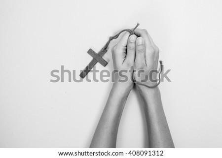 Hands of praying young woman on a yellow desk background. - stock photo