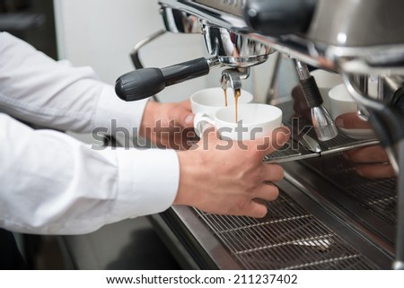 Hands of professional barista holding the white cups waiting when they fill up - stock photo
