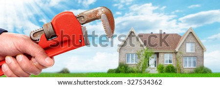 Hands of professional Plumber with a wrench. Plumbing and renovation. - stock photo