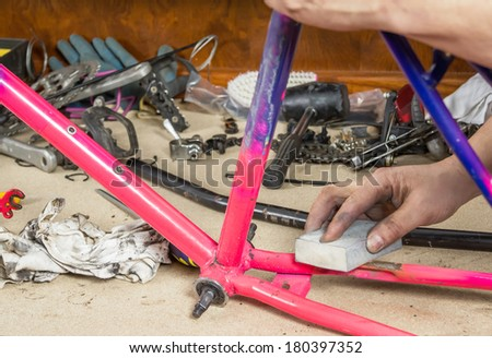 Hands of real bicycle mechanic sanding damaged frame bike in a workshop