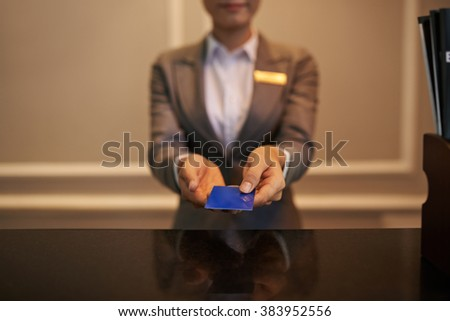 Hands of receptionist giving smart card to you - stock photo