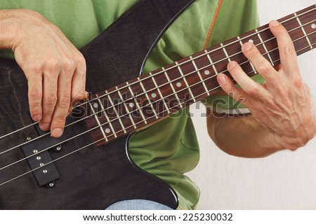 Hands of rock musician playing the electric bass guitar - stock photo