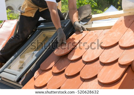 Hands Of Roofer Laying Tile On The Roof. Installing Natural Red Tile. Roof  With