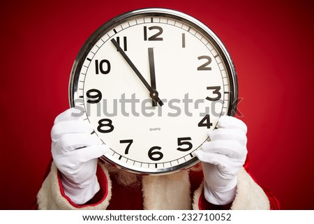 Hands of Santa holding clock with five minutes to twelve - stock photo