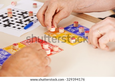 Hands of senior people playing Bingo together in a nursing home - stock photo