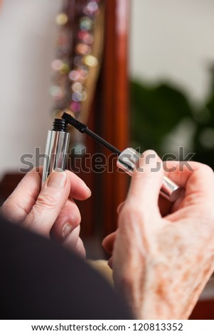 Hands of senior woman doing make-up in front of mirror.