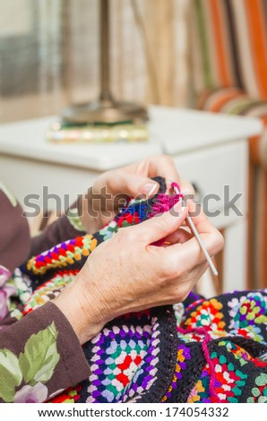 Hands of senior woman knitting a vintage wool quilt with colorful patches - stock photo