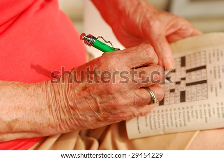 Hands of senior woman solving a crossword puzzle. - stock photo