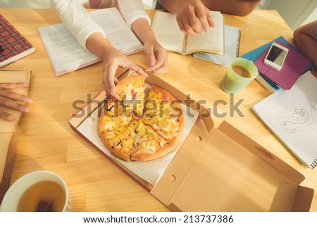 Hands of students eating pizza while preparing for exam, view from above - stock photo