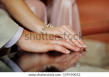 hands of the bride and groom together - stock photo