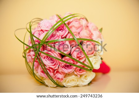 Hands of the bride and groom with rings on bouquet of roses yellow