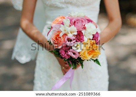 hands of the bride beautiful wedding bouquet. - stock photo