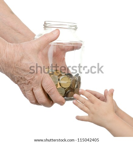 hands of the elderly person hand over to glass jar with coins in hands of the child. isolated on white background