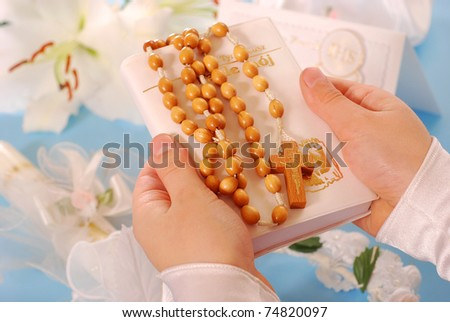 hands of the girl going to the First Holy Communion keeping a  prayer book and a  rosary - stock photo