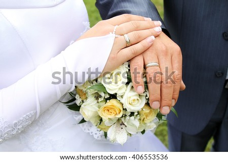 Hands of the groom and bride with rings and bridal bouquet - stock photo