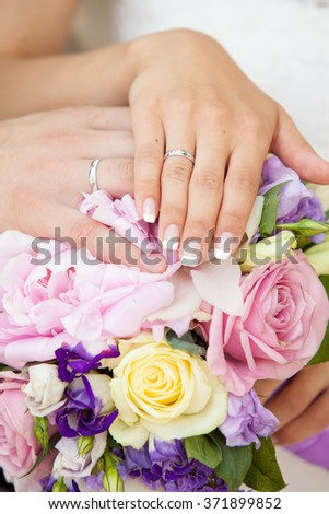 hands of the groom and the bride on a wedding bouquet from roses of pink color