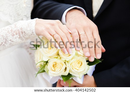 hands of the groom and the bride on a wedding bouquet from roses of yellow color - stock photo
