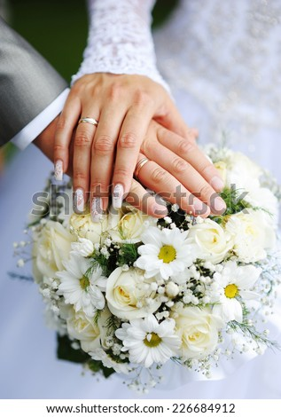 Hands of the groom and the bride with wedding rings and a wedding bouquet from roses. - stock photo