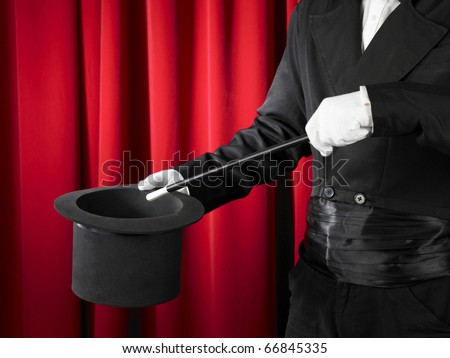 Hands of the magician with magic wand and top hat. - stock photo