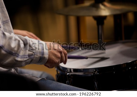 Hands of the man playing a drum set in dark colors  - stock photo