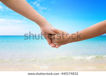 Hands of the mother and baby. Walk hand in hand. Symbolic warmth of family Displaying the love of family mother and children. Ocean blurred in the background