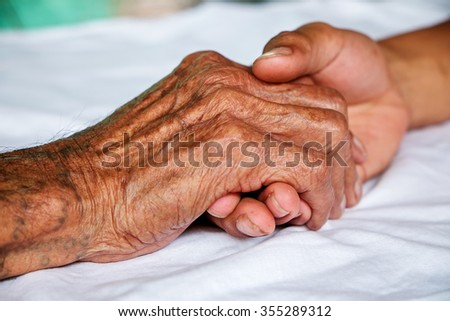 Hands of the old man and a young man - stock photo