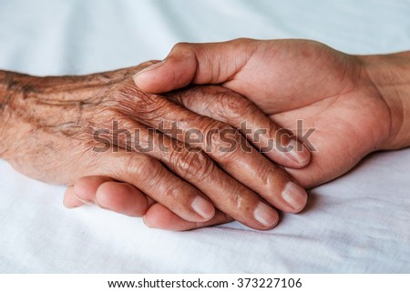 Hands of the old man and a young man on a white bed in a hospit