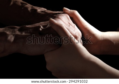Hands of the old man and a young woman. in low key. toning - stock photo