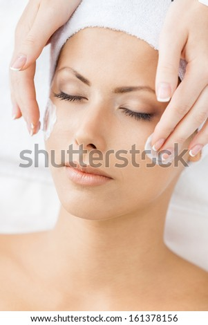 Hands of therapist apply cream to face of girl. Concept of treatment and youth - stock photo
