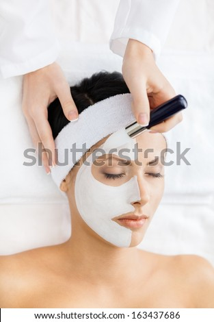 Hands of therapist apply cream to half-face of woman with closed eyes. Concept of beauty and youth - stock photo