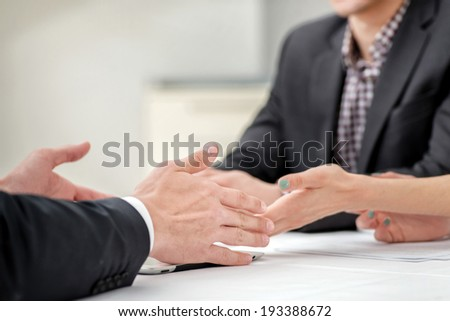 Hands of three and two businessmen discussing business affairs. Successful businessmen discussing business on a tablet. Couple man and woman sitting at the table. Close up arms - stock photo
