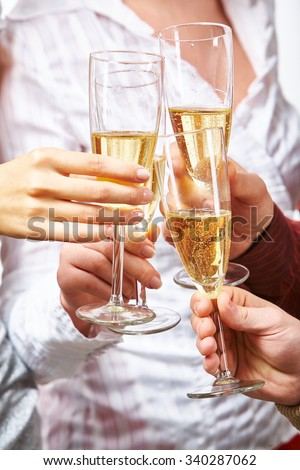 Hands of toasting friends holding flutes with champagne - stock photo