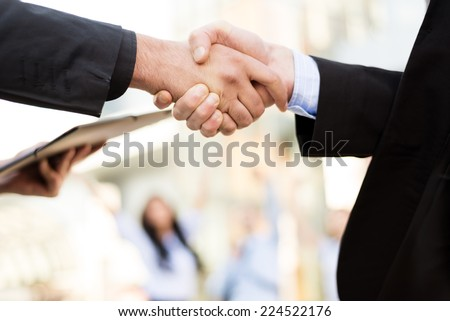 Hands of two business men shaking hands in the background can be seen by business people and office building.