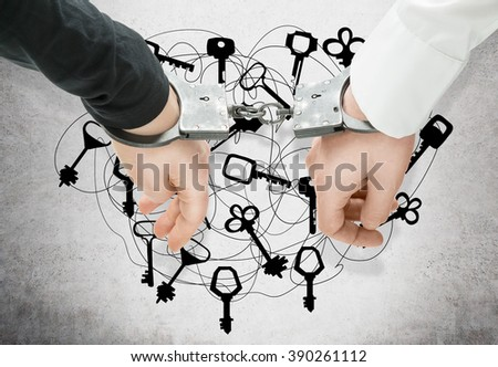 Hands of two men fixed in handcuffs. Close up. Keys at background. Concept of accessory of crime. - stock photo