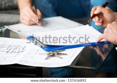 Hands of two men signed the document, sitting at the desk - stock photo