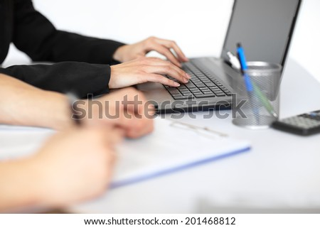 Hands of two young businesspeople working at the table in contemporary office close-up