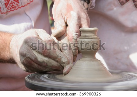 Hands of Ukrainian ceramic master and his disciple  during clay workshop. Closeup shot of hands making clay product - stock photo